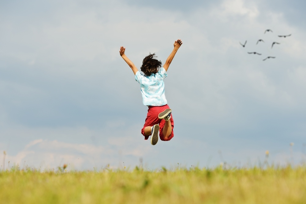Happy little boy on summer grass meadow in nature jumping.jpeg